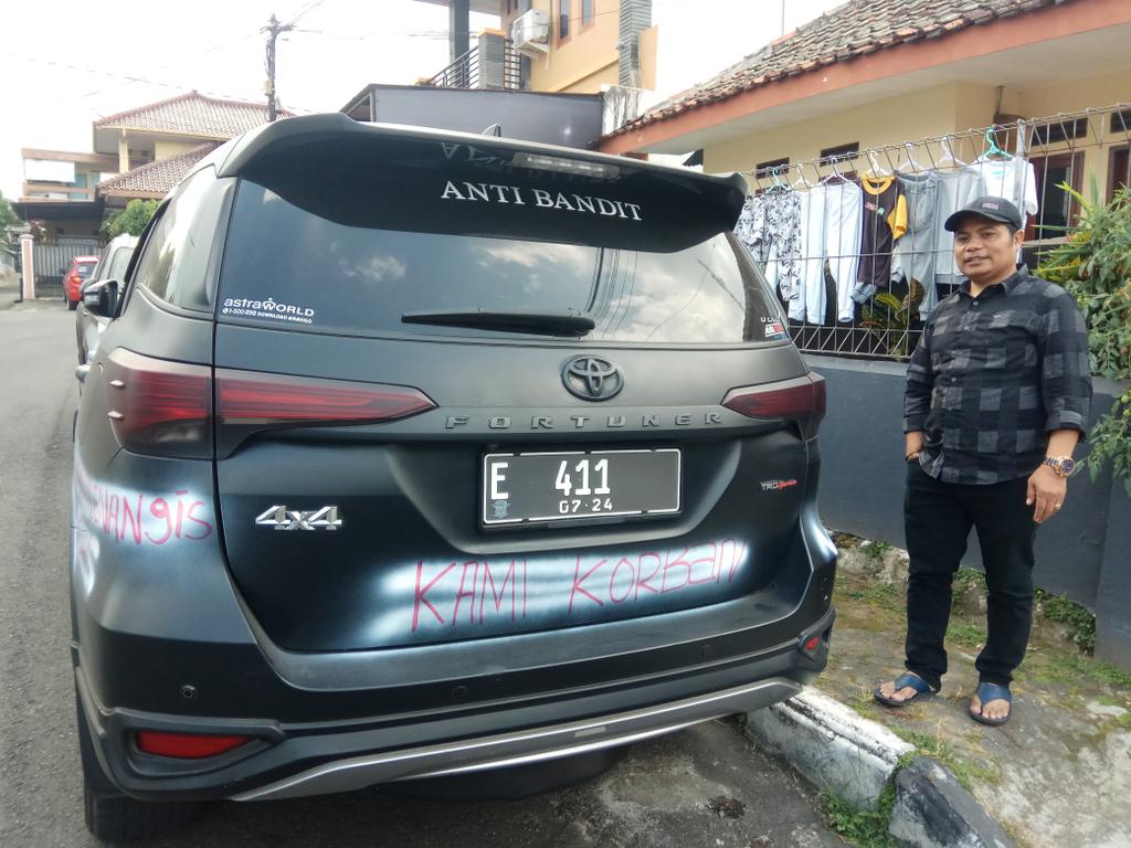 Ali Action, pengusaha kuliner asal Kuningan, Jawa Barat, menunjukkan mobilnya yang dicoret-coret sebagai bentuk protes terhadap penerapan PPKM Darurat. (Indramayujeh/Andri)