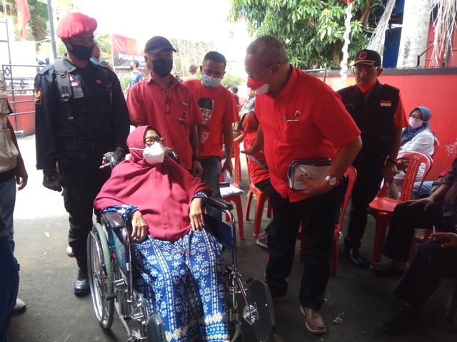 Ketua DPC PDIP Kuningan Acep Purnama menghampiri seorang warga yang akan menjalani vaksinasi corona. (Indramayujeh)