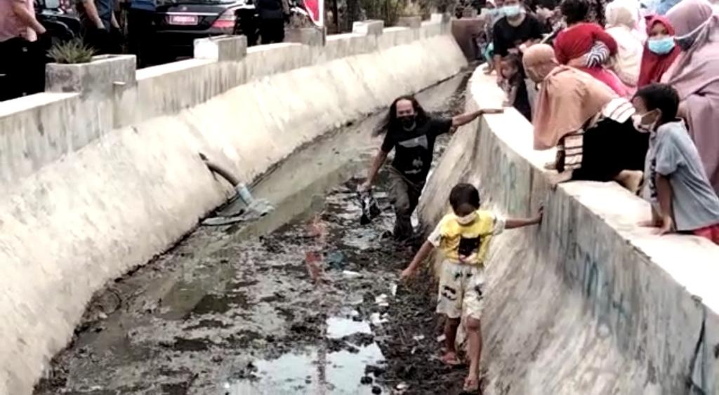 Warga rela nyebur ke saluran air demi menndapat bingkisan dari Presiden Joko Widodo. (Indramayujeh)